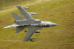 Low level tornado jet fighter. Low level Tornado GR4 jet fighter flying over green fields in countryside, Wales stock image
