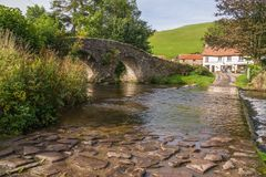 Low level view of the ford and ancient bridge at Malmsmead. Showing wet cobblestones, reflections on the water of the ford and the ancient bridge to the left Royalty Free Stock Photography