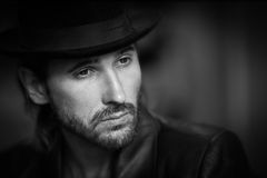 Low light black and white photo of a bearded stylish man. In a coat and hat Stock Photo