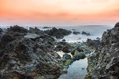 Low light long exposure scenery of Sunset over rocky beach Royalty Free Stock Images