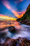 Low light long exposure scenery of sunset on the rocky beach wit. H misty wave Royalty Free Stock Photos