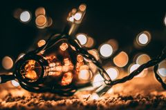 Low-light Photo of Amber Glass Bottle With String Lights and Beige Bokeh Stock Photography
