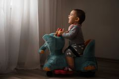 Low light photo of todler baby playing indoors at home on the elephant toy happy memories. Low light photo of todler baby playing indoors at home on the elephant royalty free stock images