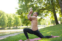 Low lunge with garudasana hands. Profile of sporty Indian young man warming up, doing stretching exercises, standing in low lunge on river bank in park with royalty free stock photos