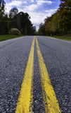 Low Middle Road. A low shot of a country road with focus on the road close to the camera Royalty Free Stock Image