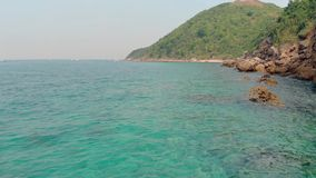 Low motion over perfect blue ocean water by green island. Low motion above perfect clear blue water near green hilly island with forest and large brown beach stock video footage