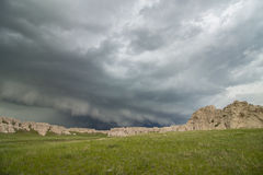 A low and ominous shelf cloud approaches rocky bluffs on a hillside. Royalty Free Stock Image