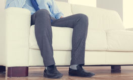 Low part of classy businessman sitting on cosy sofa Stock Photo