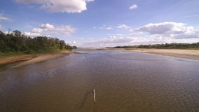 Low pass over Vistula river in Warsaw in Poland. Low pass over water of Wisła river in Poland. Flight over beaches near nature reserve. Video made during stock footage