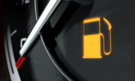 Low Petrol Dashboard Light. A 3D render of an extreme closeup of an illuminated low petrol fuel dashboard light on a car dashboard panel background Royalty Free Stock Image