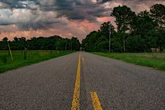 Low POV road leading into colorful clouds royalty free stock photography