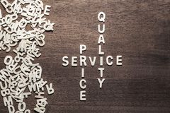 Low Price High Quality Service. Low price, hight quality service concept in crossword style, arranged from scattered wood letters Royalty Free Stock Images
