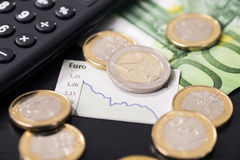 Low rate of the euro. A graphic shows the falling euro rate and is surrounded by euro coins stock image