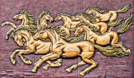 Low relief cement handcraft of horse. Stock Photos
