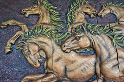 Low relief sculpture of horses on the wall. Low relief sculpture of horses on dark background on the wall Stock Photos