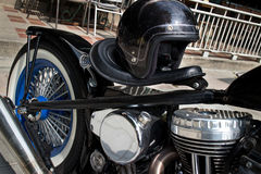 Low Rider Motorcycle with Black Helmet and Chrome. Side angle view of a custom no brand  low rider motorcycle with chrome engine and fat rear wheel; black helmet Royalty Free Stock Photo
