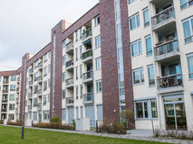 Low Rise Apartment Building with Green Lawn. Exterior of Low Rise Apartment Building with Small Balconies Surrounding Green Interior Courtyard Grounds on royalty free stock images