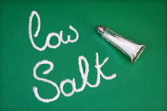 Low salt diet. Salt shaker spelling out the words low salt on green background Stock Photography