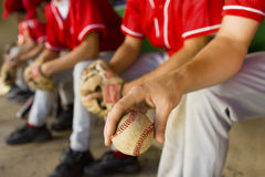 Low Section Of Baseball Team Mates Sitting In Dugout. With player holding a ball in foreground stock images