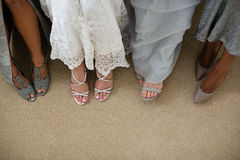 Low section of bride and bridesmaids. Standing at home stock photos