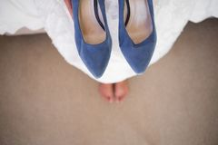 Low section of bride holding blue shoes while sitting in fitting room. High angle low section of bride holding blue shoes while sitting in fitting room Royalty Free Stock Images