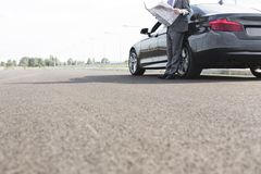 Low section of businessman with map while standing outside car on road stock photo