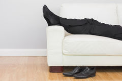 Low section of businessman resting on sofa in living room Royalty Free Stock Photos