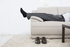 Low section of a businessman resting on sofa in living room Stock Photos
