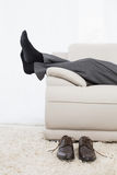 Low section of businessman resting on sofa in the living room Royalty Free Stock Photo