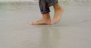 Low section of Businessman walking barefoot on the beach 4k. Low section of Businessman walking barefoot on the beach. Sea waves in the background 4k stock footage