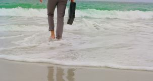Low section of Businessman walking barefoot with briefcase on the beach 4k. Low section of Businessman walking barefoot with briefcase on the beach. Sea waves in stock footage