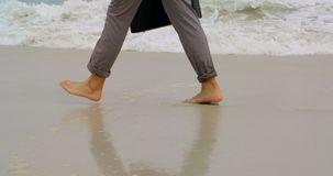 Low section of Businessman walking barefoot with briefcase on the beach 4k. Low section of Businessman walking barefoot with briefcase on the beach. Sea waves in stock video