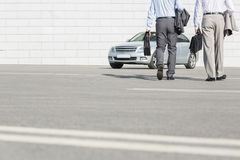 Low section of businessmen carrying briefcases while walking towards car on street Royalty Free Stock Images