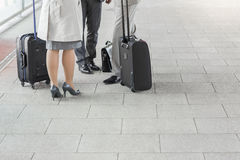 Low section of businesspeople with luggage standing on railroad platform Stock Photos