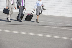 Low section of businesspeople with luggage walking on street Stock Photo