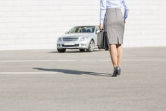 Low section of businesswoman carrying briefcase while walking towards car on street Royalty Free Stock Photography