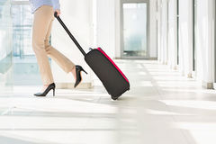 Low section of businesswoman with luggage exiting airport Royalty Free Stock Photos