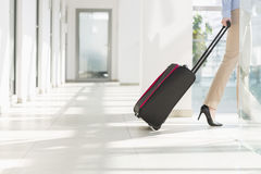 Low section of businesswoman with luggage leaving airport Royalty Free Stock Photography