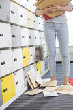 Low section of businesswoman standing by fallen documents in locker room at creative office Royalty Free Stock Image