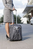 Low section of businesswoman standing with luggage on driveway Stock Images