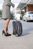 Low section of businesswoman standing with suitcase on driveway Royalty Free Stock Images