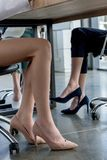 Low section of businesswomen in high heeled shoes sitting. At table royalty free stock image
