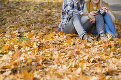Low section of couple with camera sitting on autumn leaves in park Stock Images
