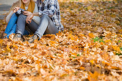 Low section of couple with camera sitting on autumn leaves in park Royalty Free Stock Images