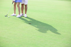 Low section of couple playing golf at course Stock Images