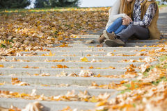 Low section of couple sitting on steps in park during autumn Royalty Free Stock Photo