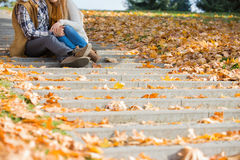 Low section of couple sitting on steps in park during autumn Royalty Free Stock Photography