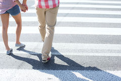 Low section of couple walking on crosswalk Royalty Free Stock Image