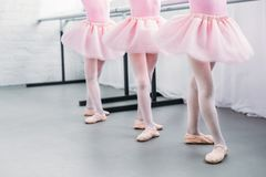 Low section of cute little kids in pink tutu skirts and ballet shoes dancing in studio stock photo