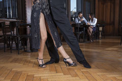 Low Section Of Dancers Doing Tango In Restaurant. Low section of dancers doing tango while mid adult couple dating in restaurant Royalty Free Stock Images